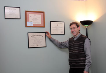 Dr. Maryott with degrees and diplomas in his office